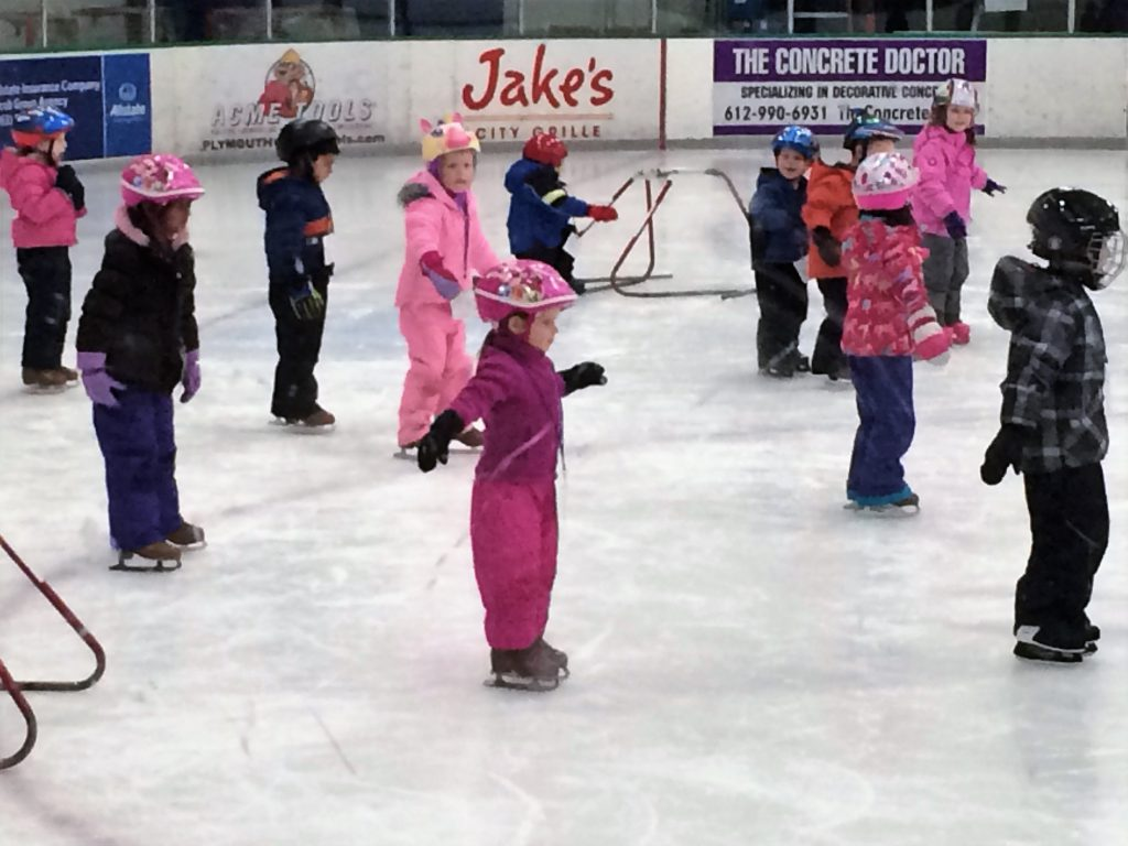 Young beginner ice skaters make progress during group lessons