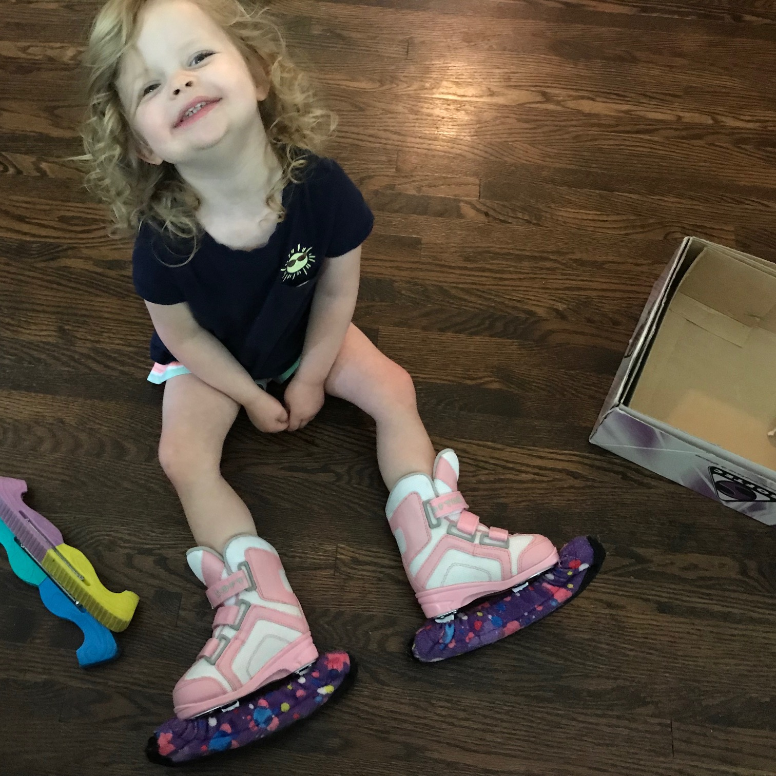 TinyTot is all smiles when she tries on her new skates